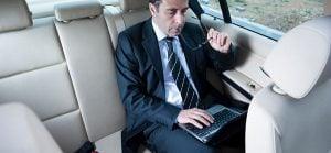 Imagine cu un pasager lucrand la calculator pentru serviciul de inchirieri auto cu sofer - servcii pentru companii